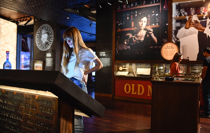 a woman engaging with an interactive exhibit at the Sazerac House