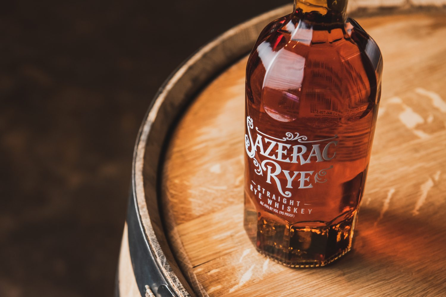Bottle of Sazerac Rye sitting on top of a whiskey barrel.
