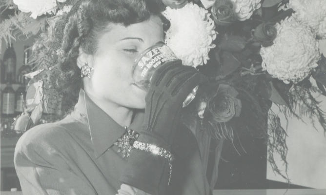 Black and white vintage photo of woman drinking out of a Sazerac glass