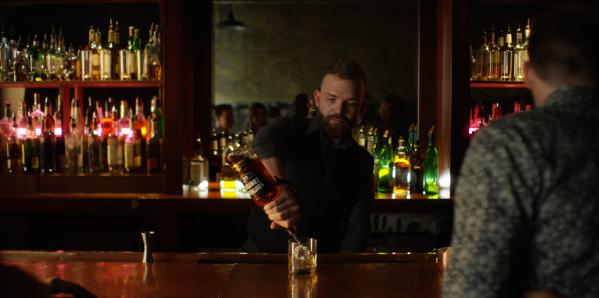 Bartender pours drink in dimly lit bar